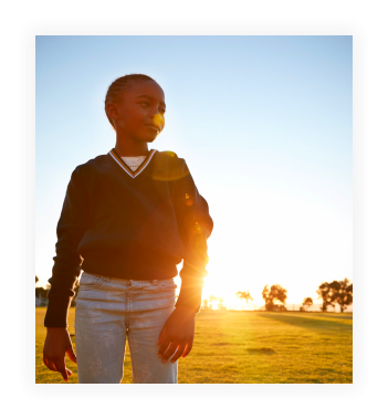 African elementary school girl in a park at sunset